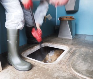 Raking the compost in twin vault toilet
